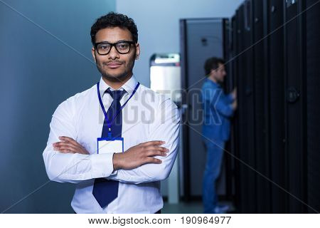 I am a professional. Smart intelligent nice man crossing his hands and looking at you while working as a technician in the data center