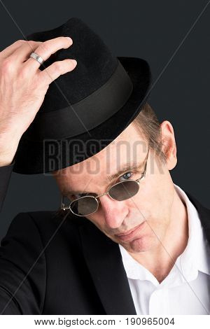 Headshot portrait of a sympathetic adult european male lifting his hat and business suite