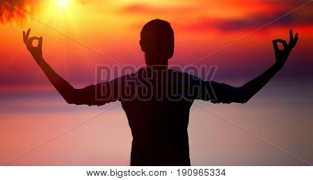 Silhouette of a woman doing yoga exercise over beautiful sunset background, soul peace and harmony, mental and physical health concept