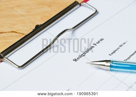Resignation form with pen on wood desk background