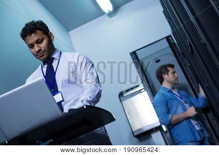 Being online. Confident hard working serious man standing in front of the laptop and checking the Internet connection while doing his job