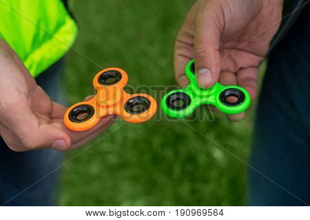 trendy fidget spinner - two persons holding green and orange fidget spinners in hands, close up view