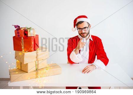 A portrait of a handsome santa claus giving presents