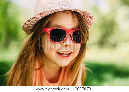 Portrait of a little cute girl wearing a hat and sunglasses outdoors