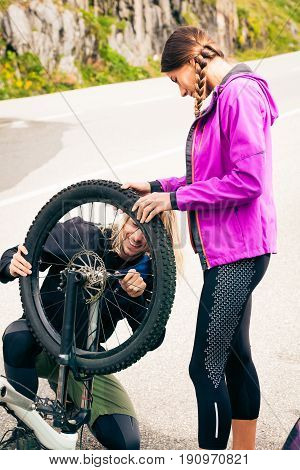 Young Couple Getting Their Bikes Ready. Shot taken in Switzerland, near Rhone Glacier and Furka Pass.