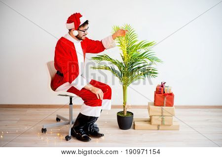 A portrait of santa claus decorating a small tree