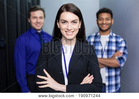 Team leader. Joyful delighted attractive woman standing in front of her colleagues and smiling while being a team leader