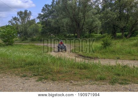 On a twisting gravel path on a glade, against the background of green trees, the ATV with the driver and the passenger goes. Both in protective helmets. Krasnodar Krai.