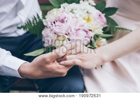 close up man holds woman hand while sitting on the bench in another hand woman holds flowers