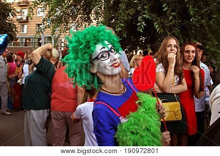 Volgograd Russia - August 26 2014: Female clown in green wig and with heart on a stick in the parade of circus performers