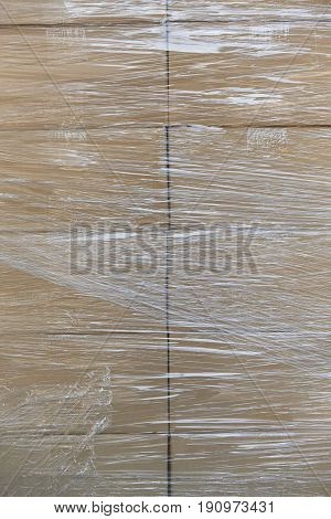 Shrink wrapping on a stacked cardboard boxes. Delivery background