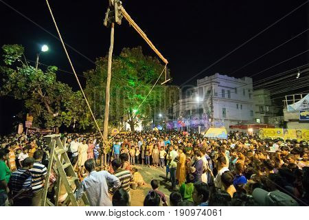 KOLKATA WEST BENGAL INDIA - 15 APRIL 2017: Pole being raised amongst spectators at night. Religious sports for festival called