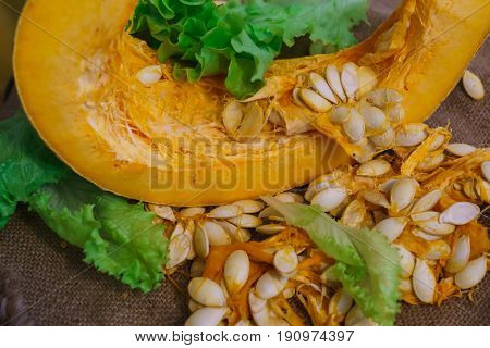 Pieces of yellow pumpkin together with seeds and greens.