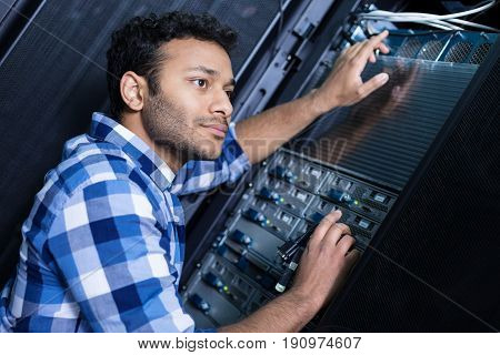 Involved in work. Nice pleasant smart man holding cables and putting them into the network server while focusing on his job