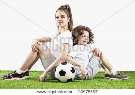 Girl and boy are sittng backs to each other on the grass with a soccer ball. Two children soccer players in sports smile over a white background