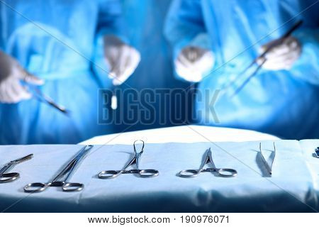 Surgical tools lying on the table while group of surgeons at background operating patient. Steel medical instruments ready to be used