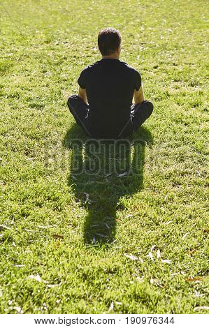 Man relaxing on the grass. Yoga Meditation outdoors. Wellness activity