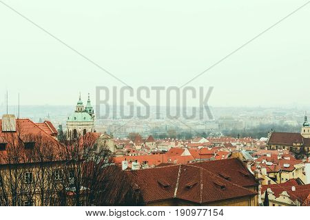 Bird's eye view of Prague skyline and St. Nicholas Church from the viewing platform near Prague Castle on a foggy winter day. Space for copy.