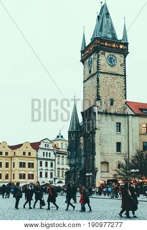 PRAGUE, CZECH REPUBLIC - FEBRUARY 11, 2017: People walk on Old Town Square, Old Town Hall and Tower on the background. The Tower is famous for its intricate astronomical clock