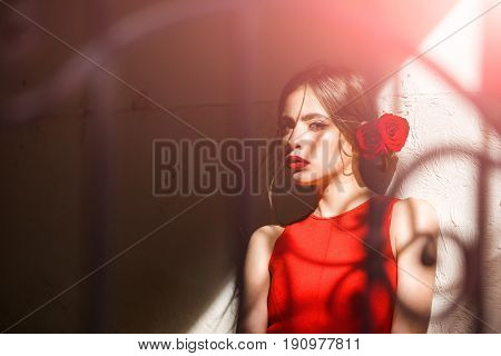 Girl In Red Dress And Roses In Hair Standing At Beige Wall