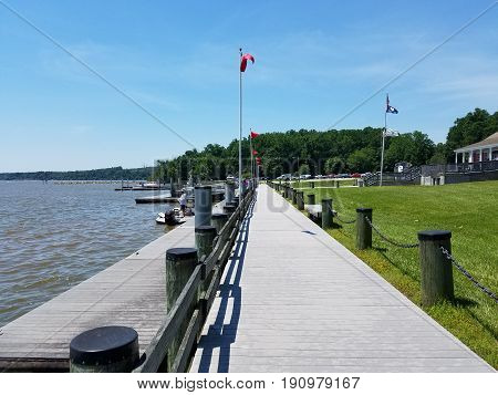 cement boardwalk and wood pier by the water