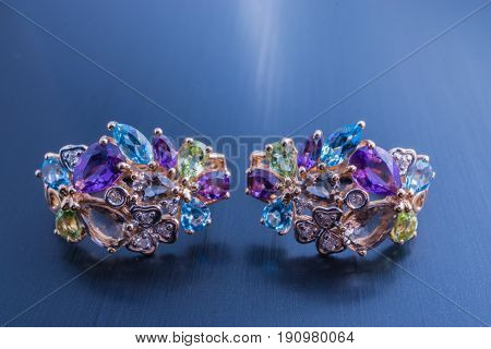 jewelry beautiful pair of gold earrings amethysts apatite peridot sapphires and other gem stones. close up shot on black background