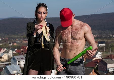 girl or pretty woman eating banana fruit. Man in red cap with bronze powder on muscular torso skin holding baseball bat. Mountain landscape. Health and sport vegetarian diet healthy dieting