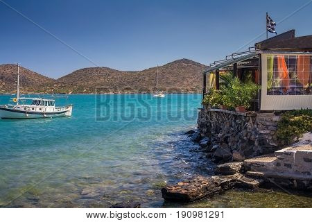 Cafe on the shore at the water's edge. Two boats are moored side by side. Low mountains in the background. Gulf of Mirabello. Elounda. Crete. Greece.