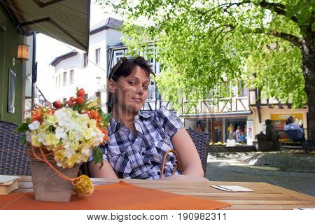 Stylish young female wearing casual shirt sitting in open air at table enjoying smelling aroma of flowers with happy expression with charming eyes waiting