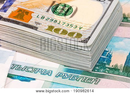 Stack of one hundred american dollar banknotes over roubles background