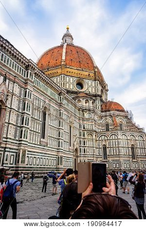 Florence Italy - June 9 2016: Tourists taking pictures of the Cattedrale di Santa Maria del Fiore (St. Mary of the Flower) in the Piazza del Duomo.