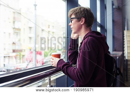 Mid shot of male in glasses talking on phone and holding cup of coffee while leaning on handrail