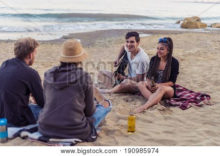 group of young and cheerful friends sitting on beach and lit bonfire. One man is playing guitar. Music on Wild beach