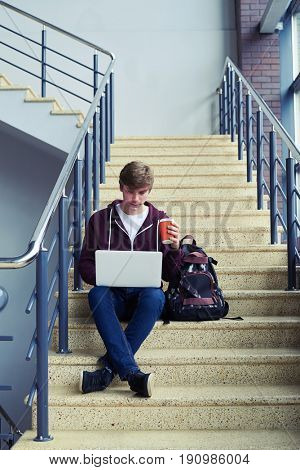 Vertical of good-looking boy holding cup of coffee and chatting in laptop while sitting on stairs with copy space