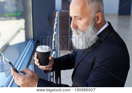 Mid shot of handsome man age of 50-60 holding cup of coffee and surfing in phone while leaning on handrail
