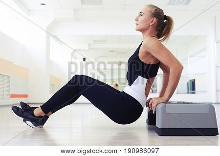 Side view of sporty woman doing press ups on step. Muscular female exercising