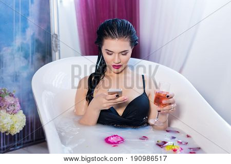 Sexy brunette woman is sitting in bath and chatting on smartphone in bathroom at home. She has s glass with champagne in hand
