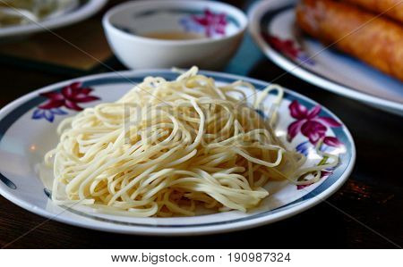 Cooked noodles in white flowered plate A plate of cooked noodles ready to be mixed with garnishing and sauces