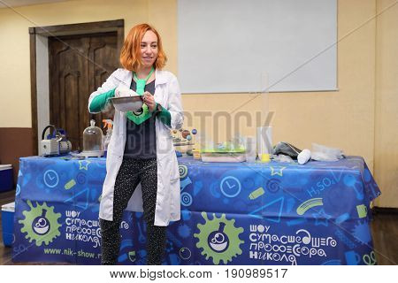 MOSCOW - DEC 18, 2016: A girl in a white coat conducts a scientific experiment in the show of the mad professor Nicolas