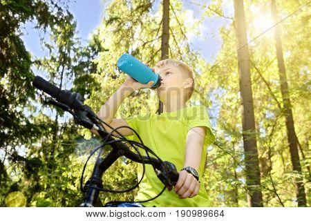 Teenager by bicycle, pine wood, summer sunny day, thirst