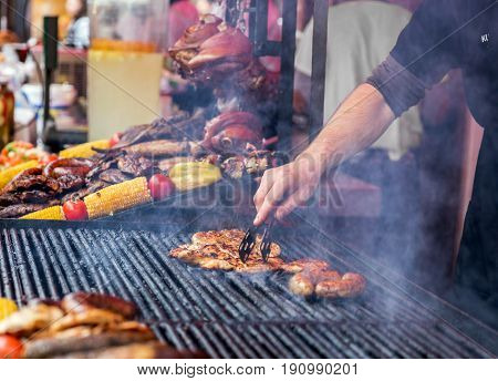 Chef is grilling perfect steak on cast iron grate. Street food