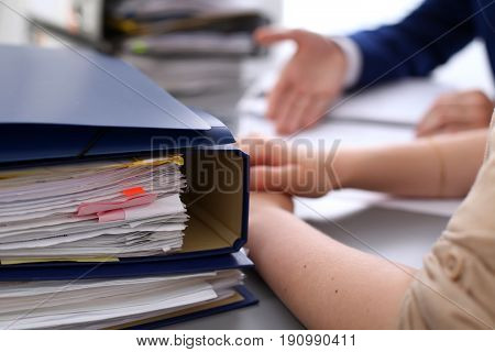 Binders with papers are waiting to be processed with businessman and secretary back in blur. Internal Revenue Service inspector checking financial document