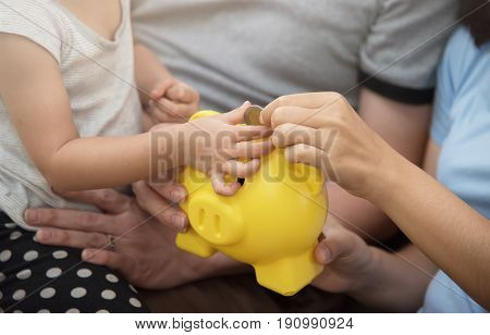 Asian little kid girl putting coin into yellow piggy bank with family.