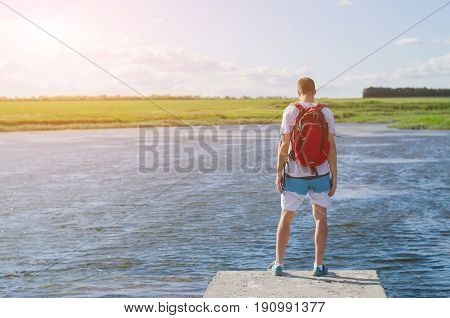 A Man With A Backpack Stands On The Edge Of The River Pier And Looks At The Sunset.