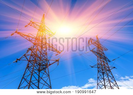 High-voltage lines against the blue sky at sunset. electricity