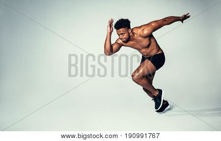 Fit Young Man Running Over Grey Background
