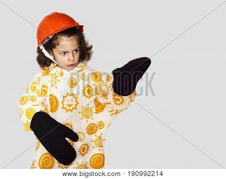 Cute Curly-haired Boy Laborer In A Raincoat Pointing His Hand. Builder In An Orange Construction Hel