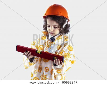 A Cute Curly-haired Boy Builder In A Raincoat Holding A Building Level.foreman In An Orange Construc