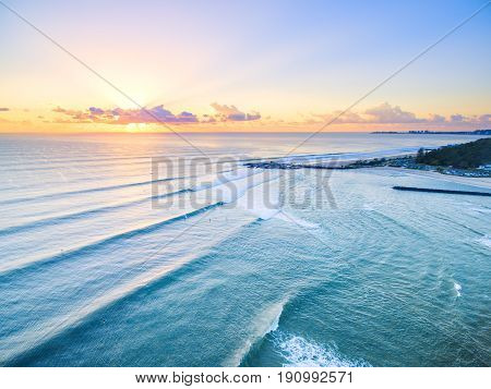 An aerial view of Currumbin Beach at sunrise with good lineup for the surfers  australiacurrumbinsurfaboveaerialaerial viewarialaustralianbackgroundbeachbeautifulbluecitycoastcolorfuldawndroneduskgoldgold coastgoldcoasthighholidaylandscapeline upnatureoce