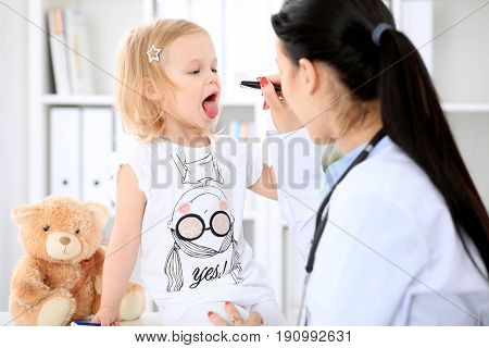 Pediatrician is taking care of baby in hospital. Little girl is being examine by doctor with stethoscope. Health care, insurance and help concept